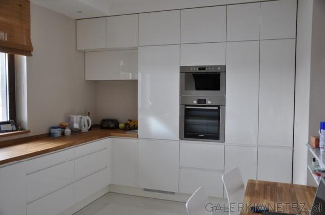 Białe szafki z mnóstwem miejsca na akcesoria kuchenne.