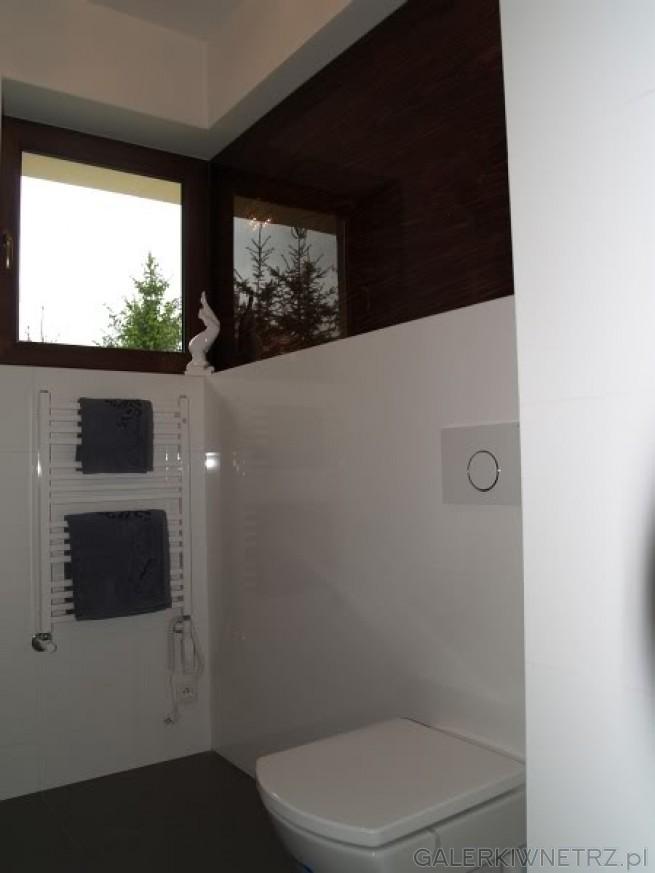 Małe,kwadratowe okno oświetlające łazienkę.Łazienka w kolorze biało-brązowym. ...