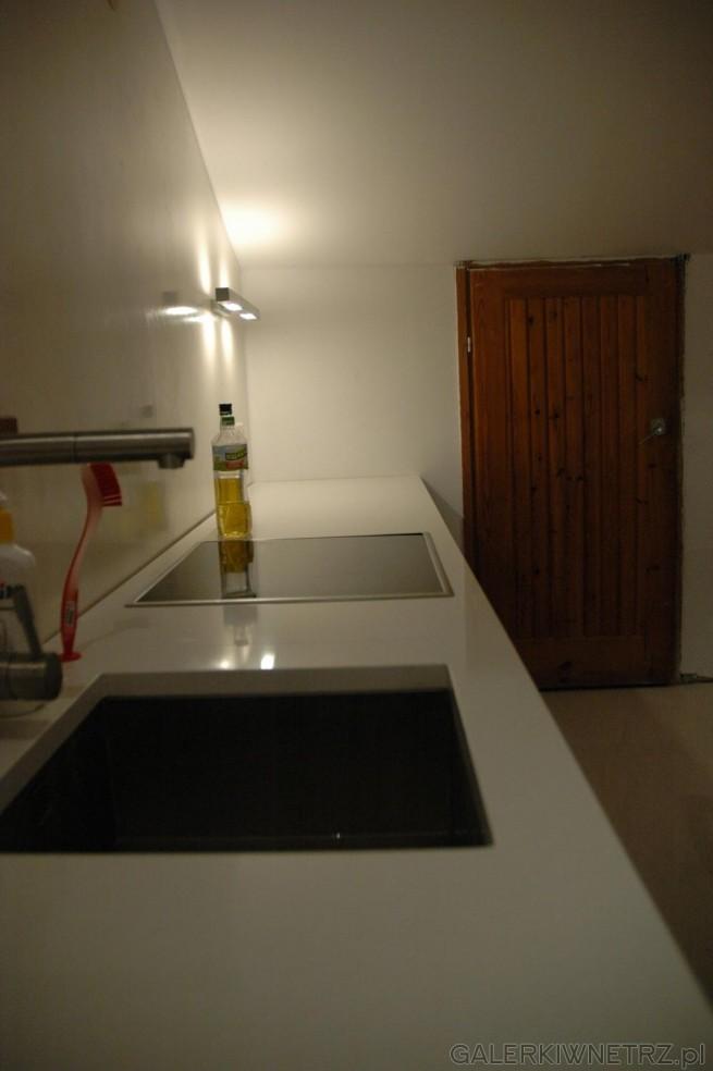 Aranżacja białej kuchni ze skosami. Na blacie z białego kwarcu znajdują się obok ...