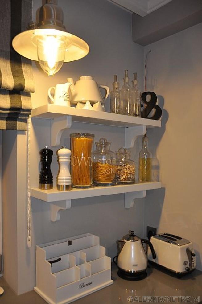 Dodatki do kuchni wykonanej w prowansalskim stylu: nad szarym blatem kuchennym znajdująsiędwie ...