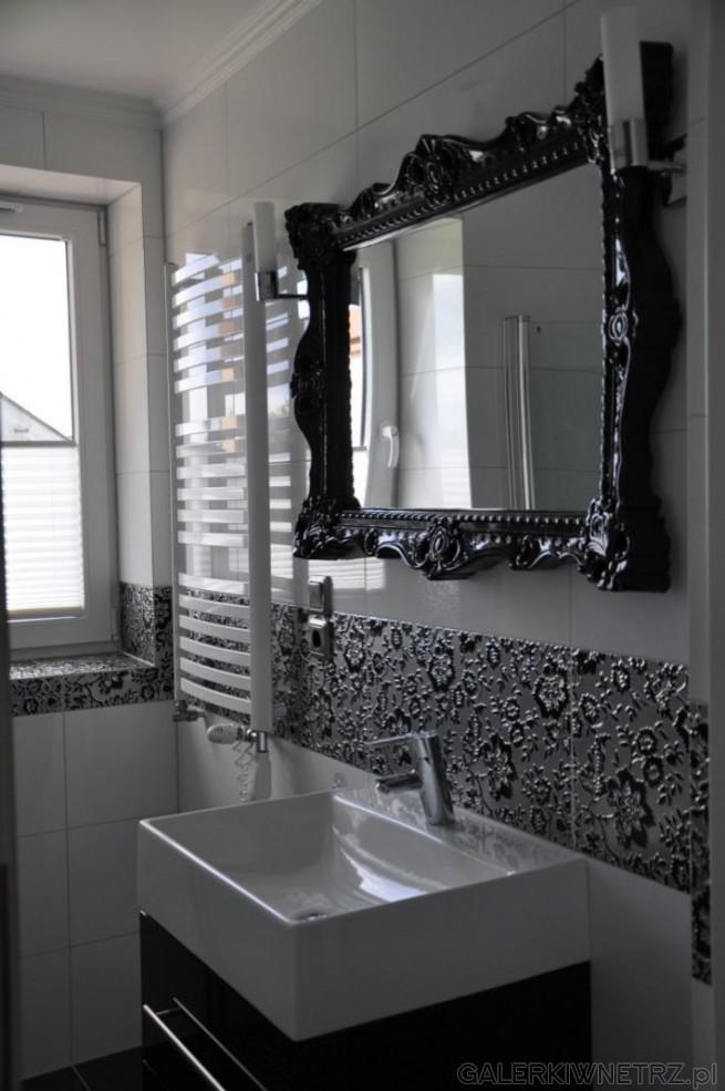 Biała łazienka z czarnymi,kwiatowymi ozdobnikami. Lustro z czarną lamówką z Norwegii.