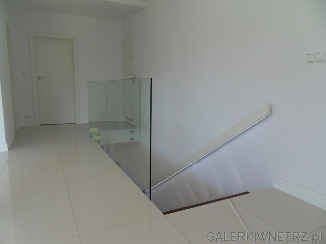 Ciemne schody zostały na górze zwieńczone szklanąbalustradą. Przez to, że balustrada ...