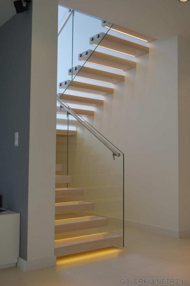 Białe schody wspornikowe są złamane w połowie. Z jednej strony okala je szklana ...