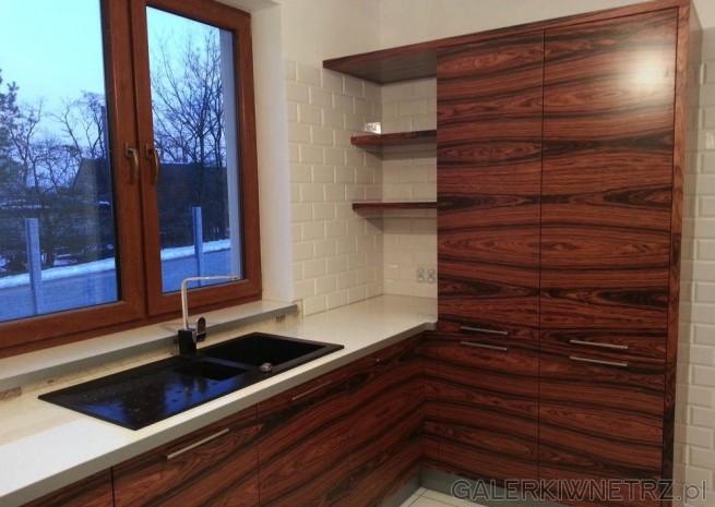 Pod oknem znajduje sięciemny zlew podblatowy. W kuchni znajdują sięteż szafki ...