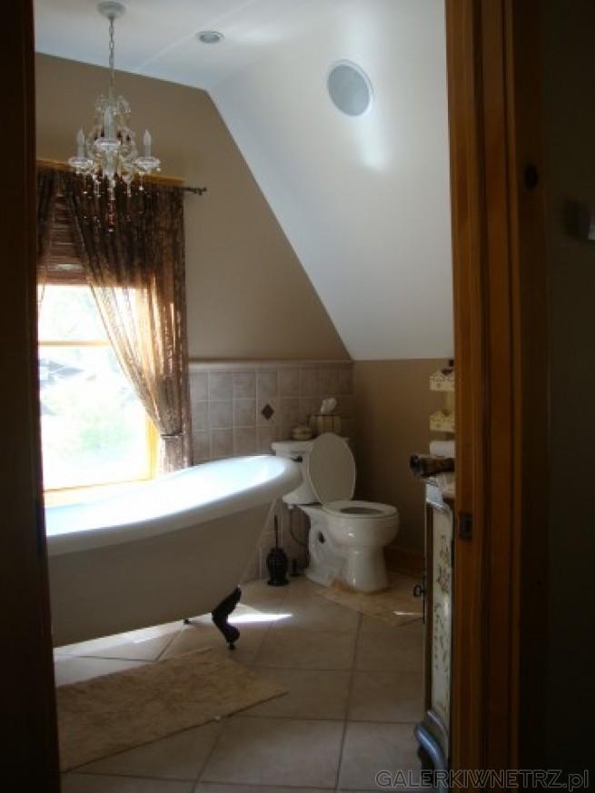 Żyrandol w łazience, kryształowy i długi. Na ziemi proste i duże płytki. Znacznie ...