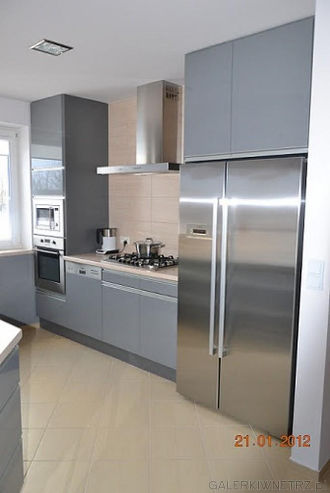 Jasna kuchnia utrzymana w szaro-metalicznej tonacji. Małe okno. Płytki na podłodze ...