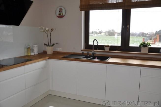 Okno oświetlające kuchnię. Białe szafki. Duża kuchnia i dobrze zagospodarowana, ...
