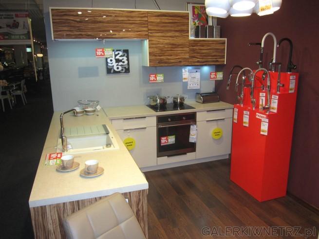 Kuchnia, w której wykorzystano szafki z ciemnobrązowymi frontami, z ciekawąfakturądrewna. ...