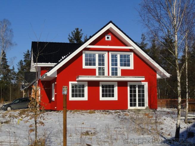 Boczna elewacja czerwonego domu. Od boku mamy wyjście na ogród przez dwuskrzydłowe ...