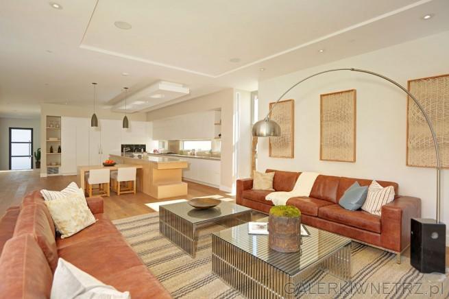 Elegancki salon gdzie dominują ciepłe barwy - przede wszystkim brązy (wpadające ...