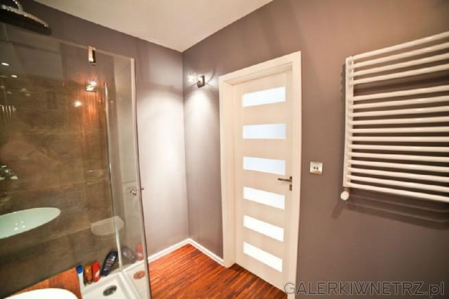 W tej aranżacji ściany zostały pomalowane na szaro, przez co łazienka jest stonowana ...