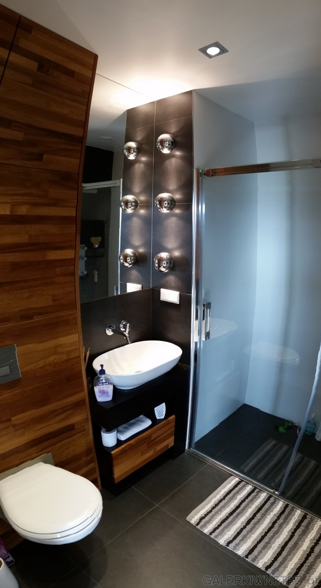 Elegancka, niewielka łazienka z dominacjąciemnych kolorów. W aranżacji wykorzystano ...