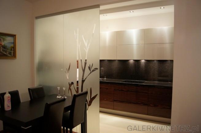 Aranżacja eleganckiej kuchni, gdzie zostały połączone jasne i ciemne kolory. ...