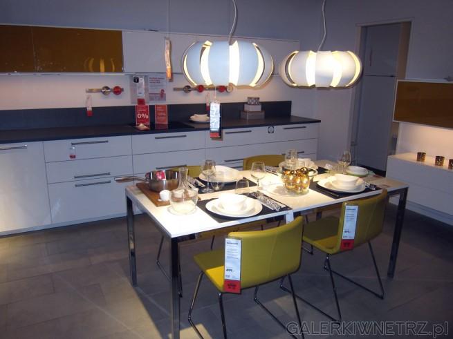 Zestaw mebli kuchennych biało-musztardowych. Kształty szafek są proste, mocnym akcentem ...