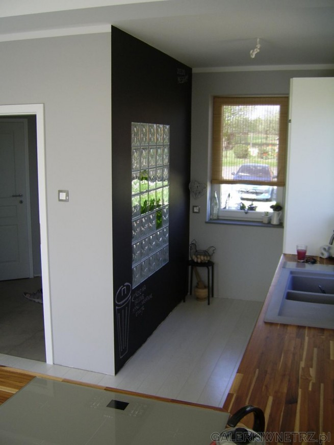 Małe okno przysłonięte roletką. Czarna ściana tablicowa
