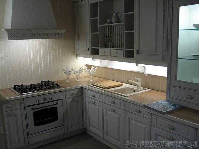 Jasna kuchnia, starzone fronty szafek. Ciekawy jest okap nad kuchnią gazową.