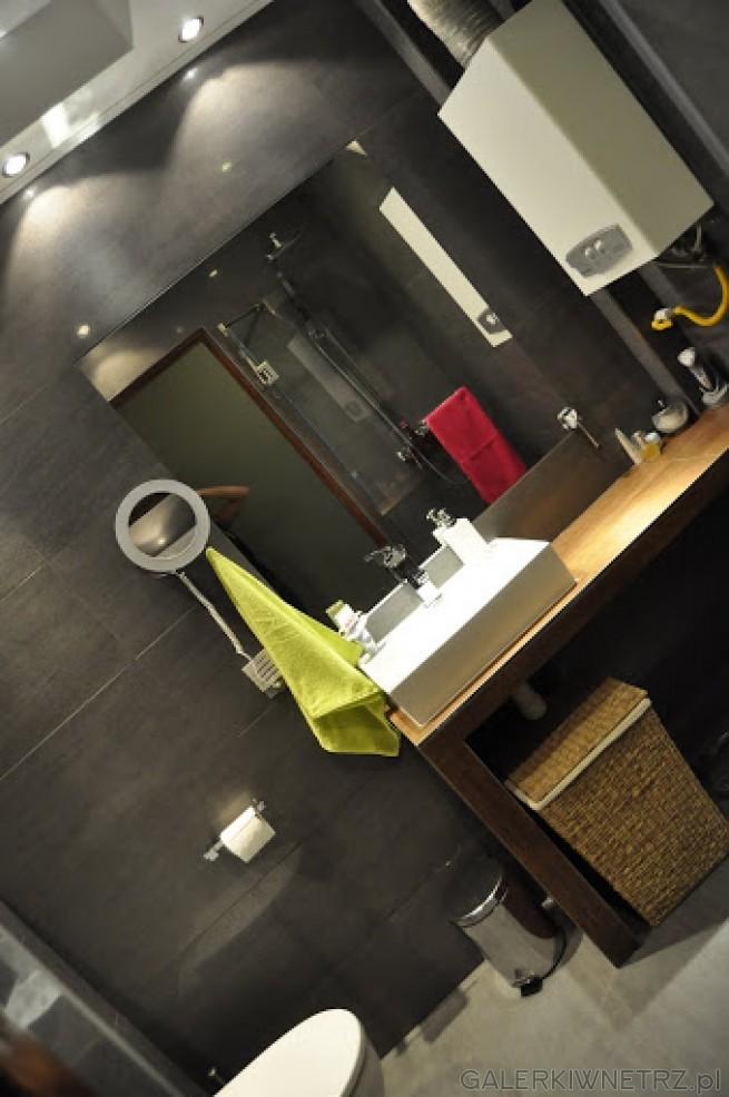 Duże lustro, umywalka na stoliku z brązowych płytek, dodaje koloru w szarym pomieszczeniu. ...