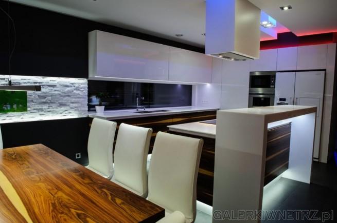 W kuchni znajduje się stół wykonany z drewna palisandrowego, przy którym znajdująsię ...