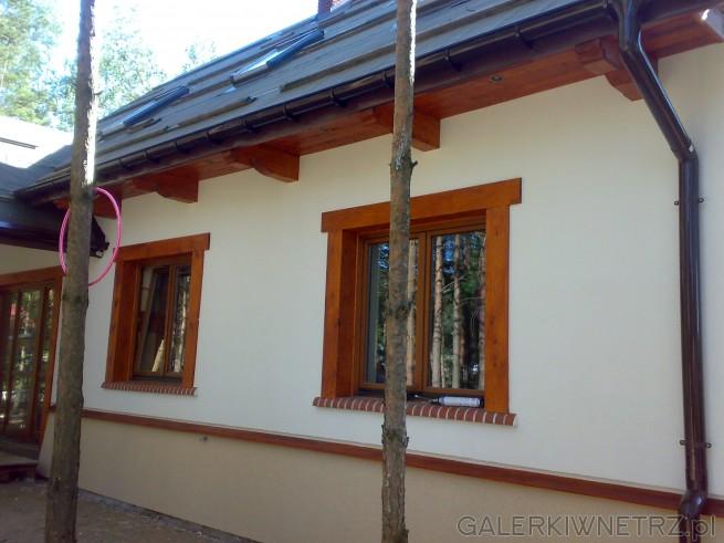 Dom w stylu rustykalnym, gdzie ozdobą elewacji jest solidne drewno w kolorze ciemnego ...