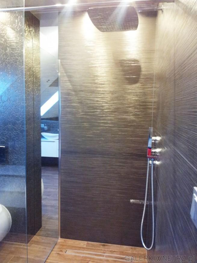 Projekt łazienki wykonany w ciemnych kolorach. Na ścianach hiszpańska glazura ...