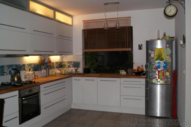 Okno przysłonięte roletą oświetla pomieszczenie w ciągu dnia. Kuchnia jest ...