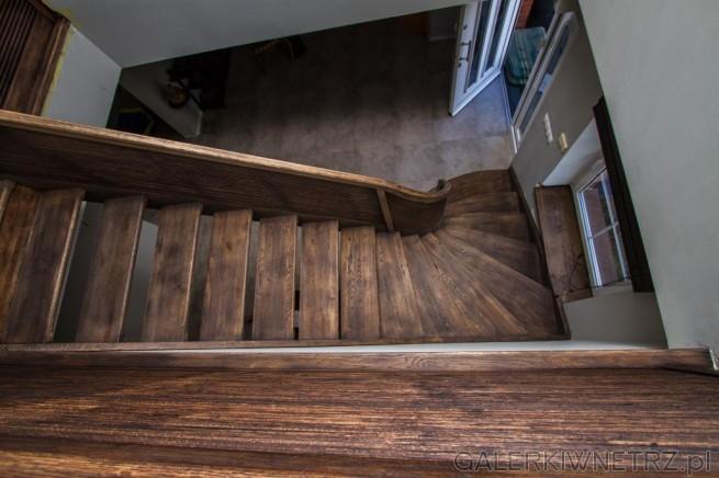 Ciekawe schody ażurowe z ciemnego drewna. Są to schody zajmujące dużo miejsca ...