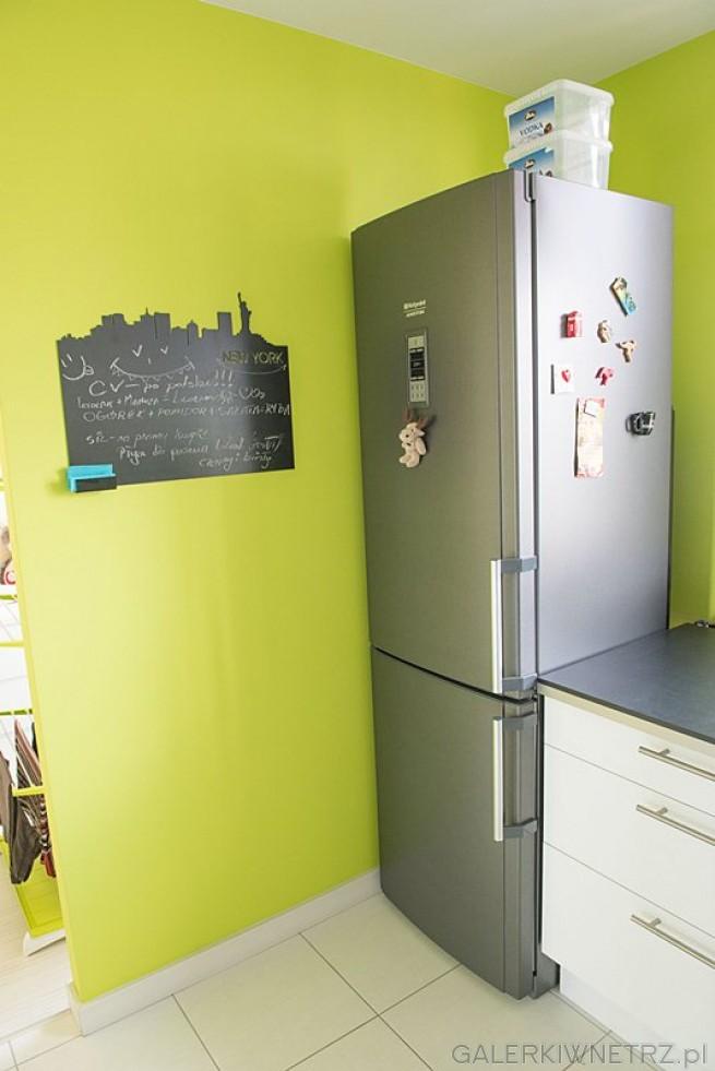 Część ścian została pomalowana na kolor limonkowy. Lodówka wraz z zamrażarkąjest ...