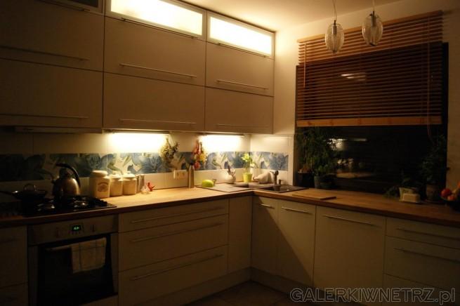 Biała kuchnia z brązowymi blatami, które ocieplają wnętrze. W oknie roleta