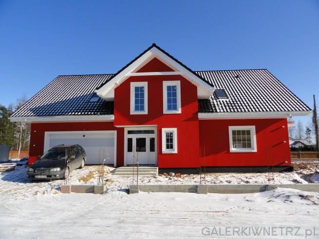 Dom z odważnąelewacją pomalowanąna kolor czerwony. Reszta elementów, takich ...