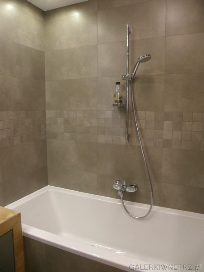 W tej łazience znajduje się wanna prostokątna, a ściany wokół niej są obudowane ...