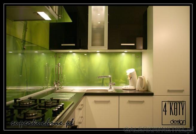 Czarny blat z laminatu. W niewielkiej kuchni znajduje si臋 lod贸wka zabudowana w ...