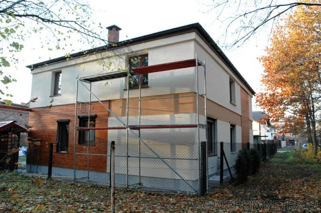 Tylna elewacja domu w beżach i drewnie. Podział elewacji na część pomalowanąoraz ...