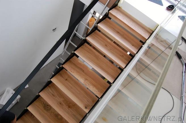 Schody ażurowe zbudowane z jasnych, drewnianych desek. Schody wydająsięlekkie ...