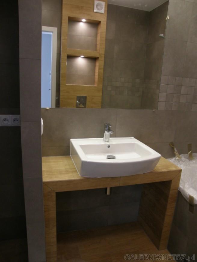 Elegancka łazienka utrzymana w kolorach brązów i szarości. Umywalka o dość ...