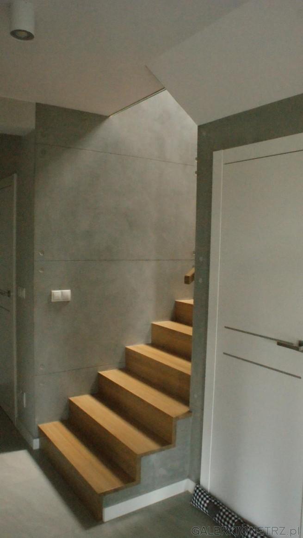Schody z drewna wpasowująsięw surową przestrzeń. Ściany przypominająsurowy beton, ...