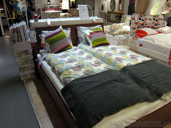 Łóżko do sypialni niskie Ikea. Rama ciemno brązowa z oparciem w takim samym kolorze.