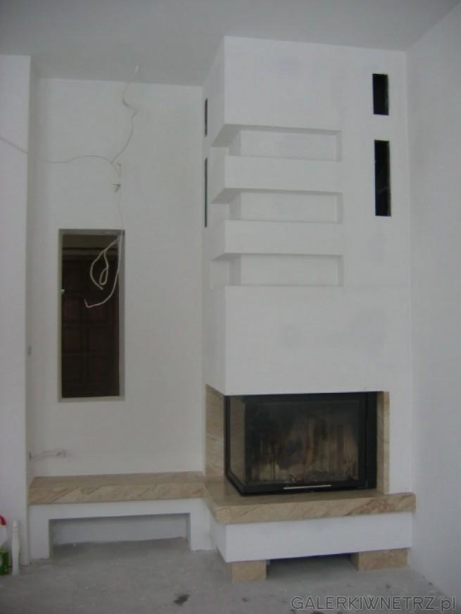 Prosty, minimalistyczny kominek narożny, który został obłożony marmurem Breccia ...