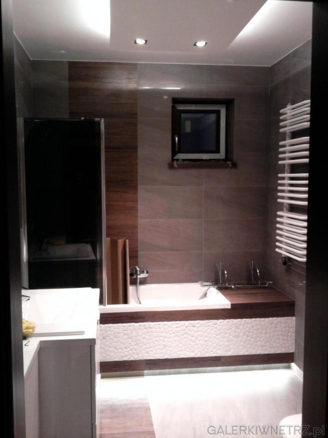 Ciemnobrązowa łazienka przełamana jasnymi elementami. Jasne elementy optycznie ...