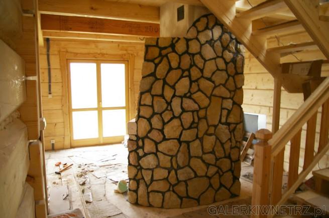 Tył kominka rustykalnego, wykonanego z dużych kawałków kamienia w kolorze jasnego ...