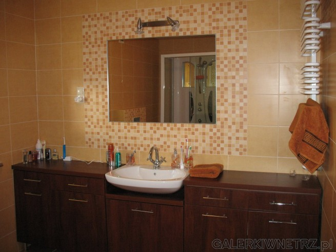Łazienka, duże lustro na środku ściany wyłożone dookoła mozaiką. Szafki na całą ...