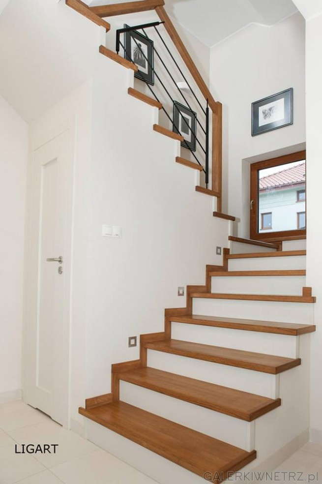 W bia艂ym pomieszczeniu znajduj膮聽si臋聽schody w bieli i w drewnie, ze stalowymi ...