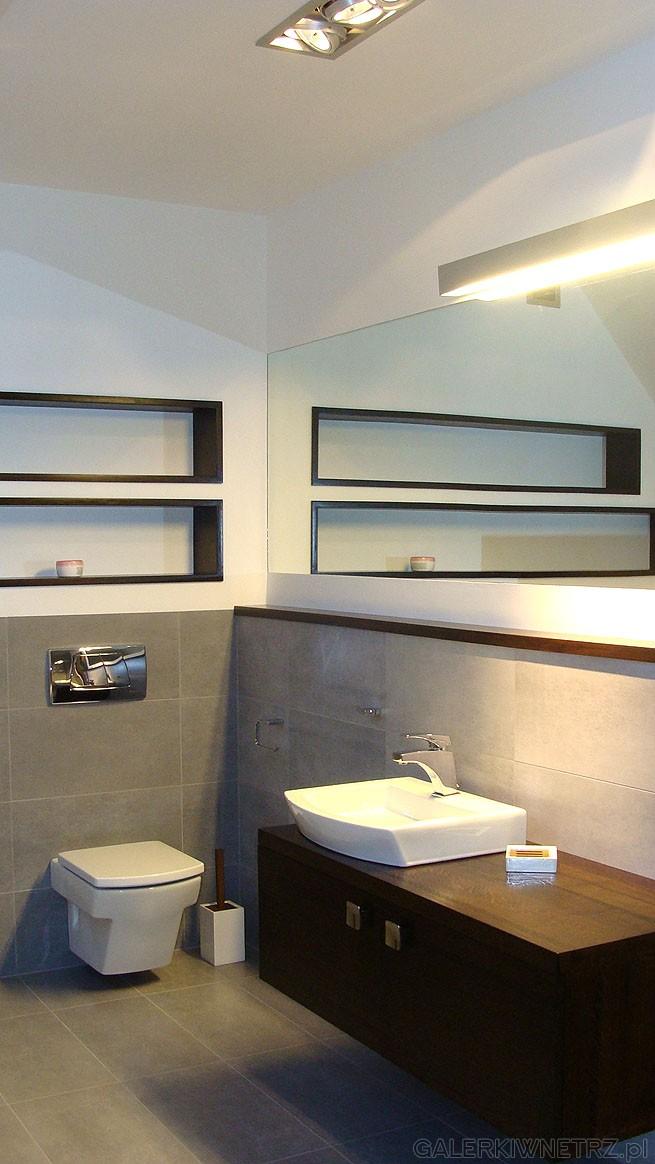 Umywalka nadblatowa na drewnianej podwieszanej szafce. Półki w ścianie są wyłożone drewnem