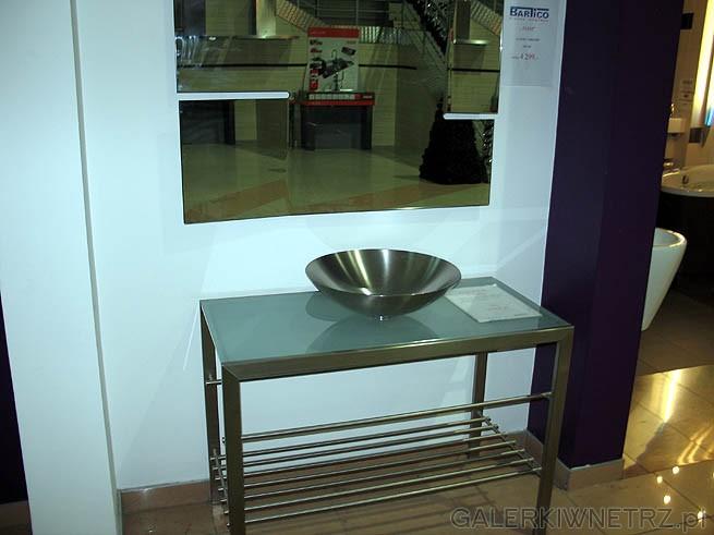 Umywalka w kształcie półmiska na skromnej szafce z metalu.