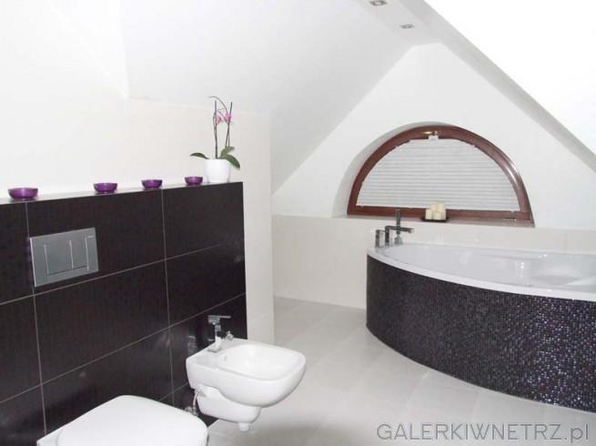 Jasna, duża łazienka ze skosami. Ciemnobrązowe, półokrągłe okienko.Na ścianie ...