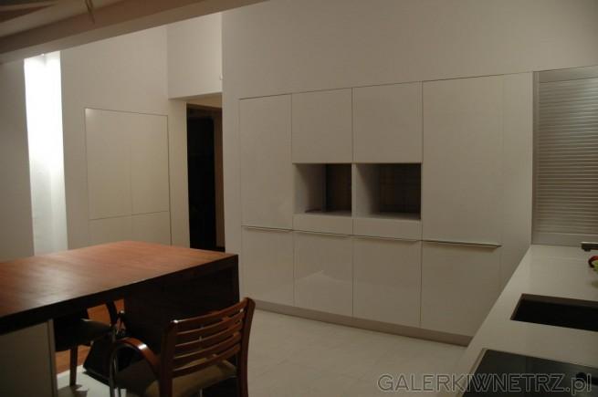 Minimalistyczna kuchnia z bielą w roli głównej. Ściany, blat i podłogi są białe, ...