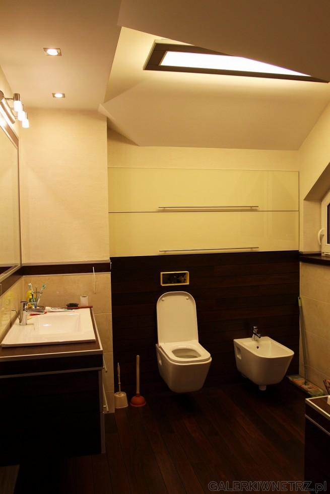 Jasna łazienka ze skosami utrzymana w ciepłej tonacji kolorystycznej. Misa wc i ...
