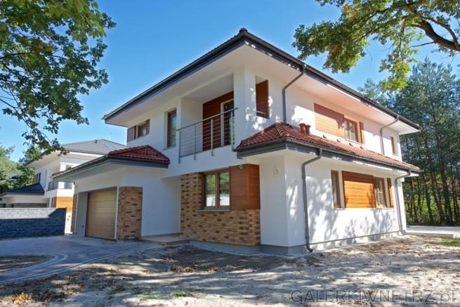 Propozycja elewacji domu dwupiętrowego z łączonych materiałów. Na elewacji ...