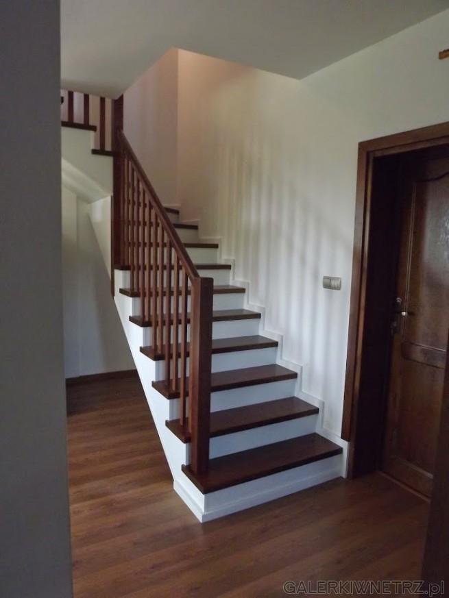 Klasyczne schody z biel膮 w roli g艂贸wnej i drewnem. Ca艂o艣膰 schod贸w jest bia艂a, ...