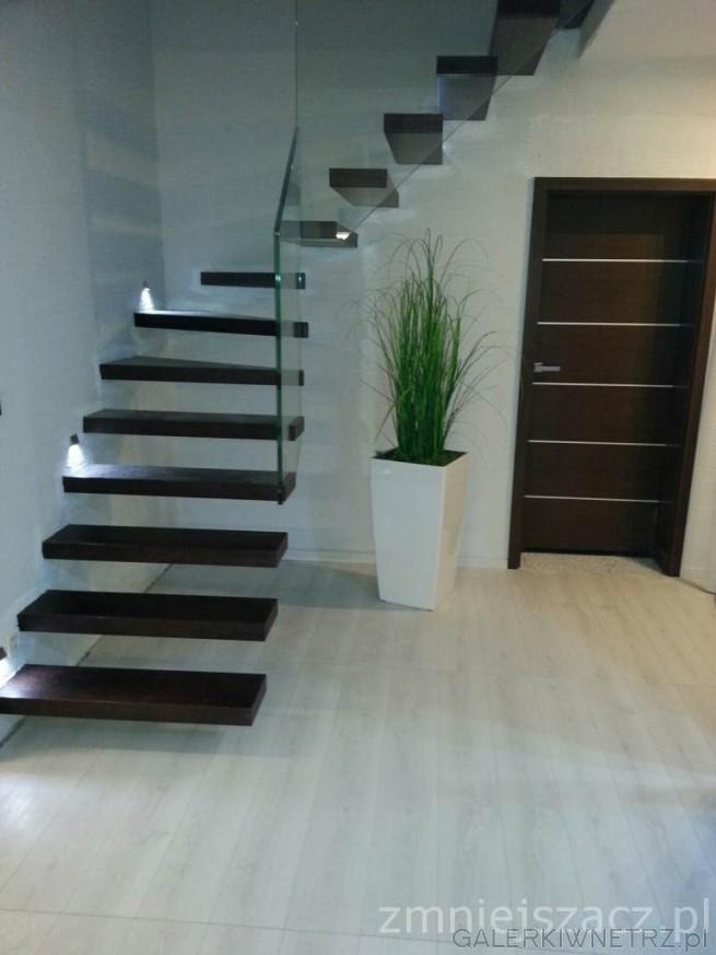 Przykład schodów gdzie zostały połączone ciemne kolory ze szkłem. Są to schody wspornikowe, ...