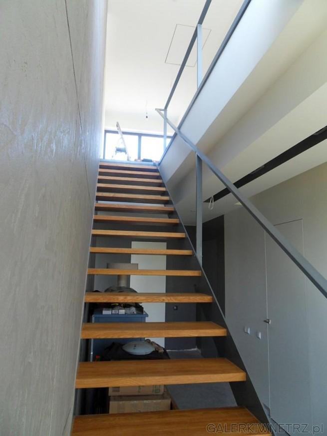 Prosty schody ażurowe, wykonane z jasnego drewna oraz z szarej poręczy. Schody ...
